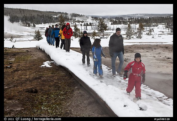 Tourists walk over snow-covered boardwalk. Yellowstone National Park (color)