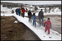 Tourists walk over snow-covered boardwalk. Yellowstone National Park, Wyoming, USA. (color)