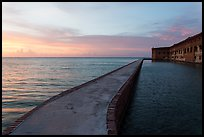 Fort Jefferson moat and walls at sunset with tourists in distance. Dry Tortugas National Park, Florida, USA. (color)