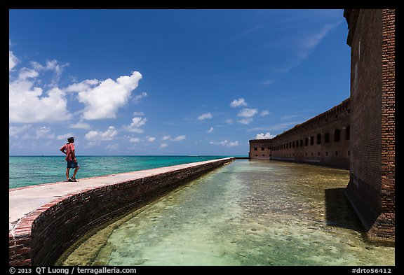 Park visitor looking, Fort Jefferson moat and seawall. Dry Tortugas National Park (color)