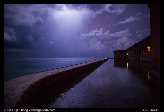 Fort Jefferson seawall at night with sky lit by thunderstorm. Dry Tortugas National Park (color)
