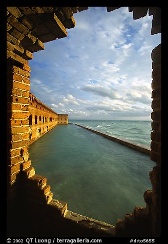 Fort Jefferson seawall and moat, framed by a crumpling embrasures, late afternoon. Dry Tortugas National Park (color)
