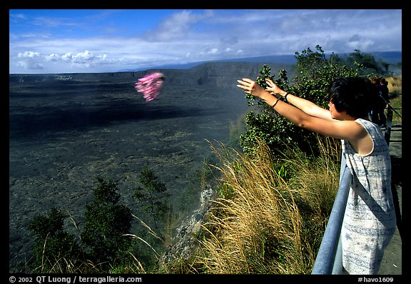 Woman throws flowers into Kilauea caldera as offering to Pele. Hawaii Volcanoes National Park (color)