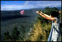Woman throws flowers into Kilauea caldera as offering to Pele. Hawaii Volcanoes National Park, Hawaii, USA.