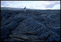 Hiker on hardened lava flow at the end of Chain of Craters road. Hawaii Volcanoes National Park, Hawaii, USA. (color)