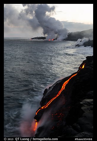 Bright molten lava flows into the Pacific Ocean, plume in background. Hawaii Volcanoes National Park (color)