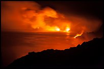 Hydrochloric steam clouds glow by lava light on coast. Hawaii Volcanoes National Park, Hawaii, USA.