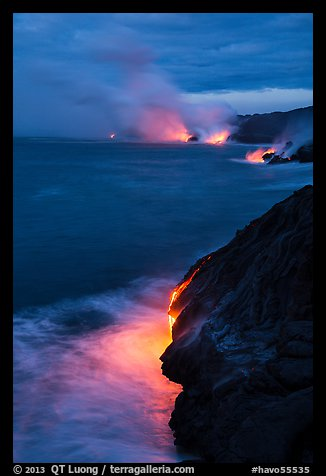 Molten lava pouring over sea cliffs at dawn. Hawaii Volcanoes National Park (color)