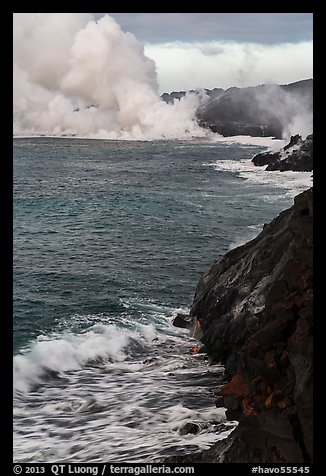 Coast with lava and clouds of smoke and steam produced by lava contact with ocean. Hawaii Volcanoes National Park (color)