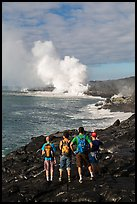Hikers looking at molten lava and coastal volcanic steam cloud. Hawaii Volcanoes National Park, Hawaii, USA. (color)
