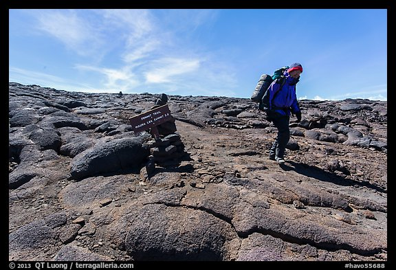 Hiker descending from Mauna Loa summit next to sign. Hawaii Volcanoes National Park (color)