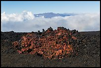 Black of colorful lava on Mauna Loa, Mauna Kea emerging from Saddle clouds. Hawaii Volcanoes National Park, Hawaii, USA. (color)