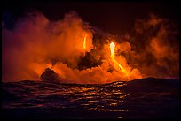 Lava cascades lighting ocean at night. Hawaii Volcanoes National Park, Hawaii, USA. (color)