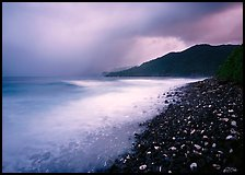 Coastline with dark rocks, light water and storm sky at sunrise, Vatia bay, Tutuila Island. National Park of American Samoa ( color)