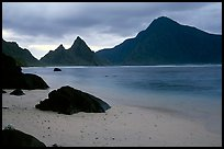 Balsalt boulders on South Beach, Sunuitao Peak and Piumafua mountain on Olosega Island in the background, Ofu Island. National Park of American Samoa