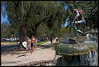 Young men carring surfboards next to statue of surfer, Kapiolani Park. Waikiki, Honolulu, Oahu island, Hawaii, USA (color)
