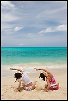 Young women doing gymnastics on Waimanalo Beach. Oahu island, Hawaii, USA ( color)