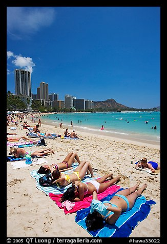 Young women on Waikiki Beach with skyline in the background. Waikiki, Honolulu, Oahu island, Hawaii, USA (color)