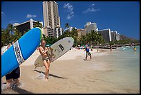 Women carrying surfboards into the water, Waikiki Beach. Waikiki, Honolulu, Oahu island, Hawaii, USA (color)