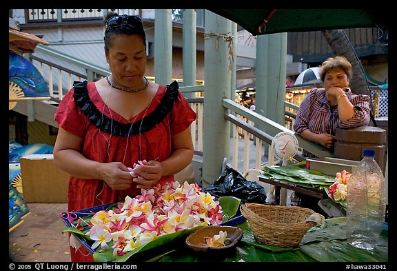 Woman preparing a fresh flower lei, with another woman looking, International Marketplace. Waikiki, Honolulu, Oahu island, Hawaii, USA (color)