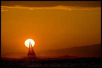 Sailboat and sun disk, sunset. Waikiki, Honolulu, Oahu island, Hawaii, USA