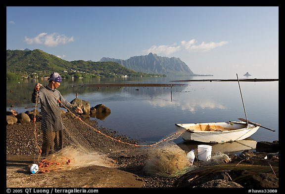Fisherman pulling out net out of small baot, Kaneohe Bay, morning. Oahu island, Hawaii, USA