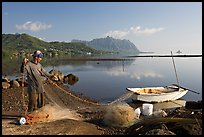 Fisherman pulling out net out of small baot, Kaneohe Bay, morning. Oahu island, Hawaii, USA ( color)