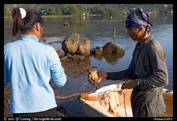 Fisherman giving a freshly caught crab to his wife, Kaneohe Bay, morning. Oahu island, Hawaii, USA (color)