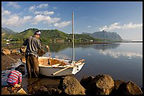 Fisherman pulling out fish out a net, with girl looking, Kaneohe Bay, morning. Oahu island, Hawaii, USA ( color)