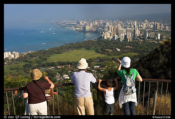 Tourists look at Waikidi from the  Diamond Head crater, early morning. Oahu island, Hawaii, USA