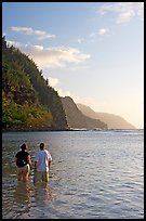 Couple looking at the Na Pali Coast, Kee Beach, late afternoon. Kauai island, Hawaii, USA