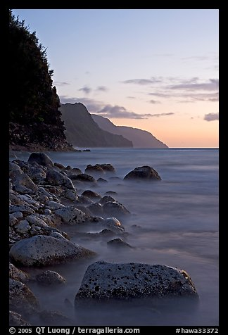 Boulders, surf, and Na Pali Coast, sunset. Kauai island, Hawaii, USA (color)