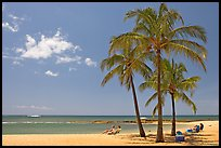 Couple on beach chair, and coconut trees,  Salt Pond Beach, mid-day. Kauai island, Hawaii, USA (color)