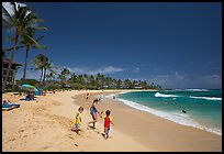 Children playing around, Kiahuna Beach, mid-day. Kauai island, Hawaii, USA