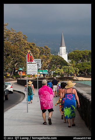 Beachgoers walking past ironman triathlon sign, Kailua-Kona. Hawaii, USA (color)