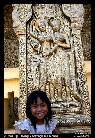 Girl and sculpture at Wat Phnom. Phnom Penh, Cambodia (color)