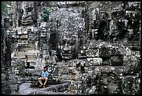Boy sits next to large stone smiling faces, the Bayon. Angkor, Cambodia