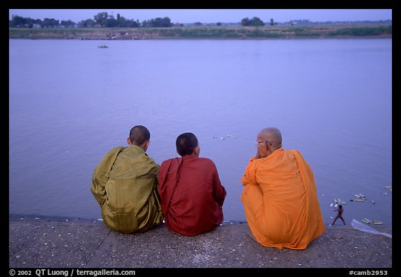 Buddhist monks sit on  banks of Tongle Sap river at dusk,  Phnom Phen. Cambodia (color)