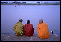 Buddhist monks sit on  banks of Tongle Sap river at dusk,  Phnom Phen. Cambodia