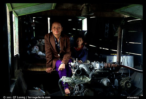 Engine and pilot at the rear of a slow passenger boat. Mekong river, Laos (color)