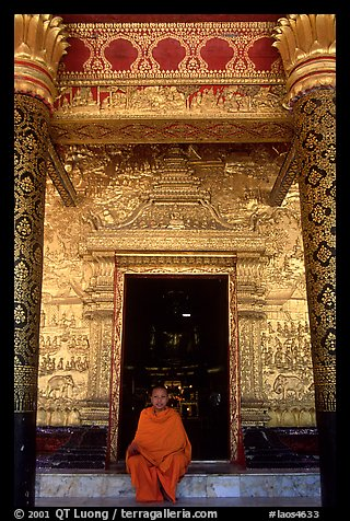 Buddhist novice monk sits at door of Wat Mai Suwannaphumaham. Luang Prabang, Laos (color)