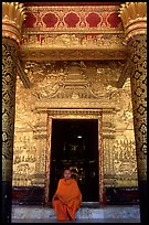Buddhist novice monk sits at door of Wat Mai Suwannaphumaham. Luang Prabang, Laos