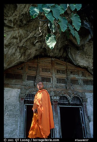 Novice Buddhist monk at entrance of lower Pak Ou cave. Laos (color)