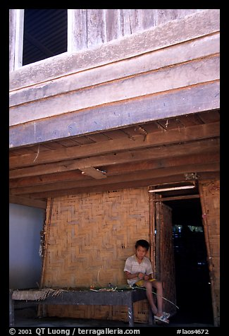 Boy at the entrance of traditional hut, Ban Xang Hai. Laos