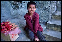 Boy sells incence sticks at the entrance of a shrine, Pak Ou. Laos ( color)