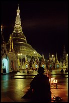 Praying at the wish-fullfilling place by night , Shwedagon Paya. Yangon, Myanmar