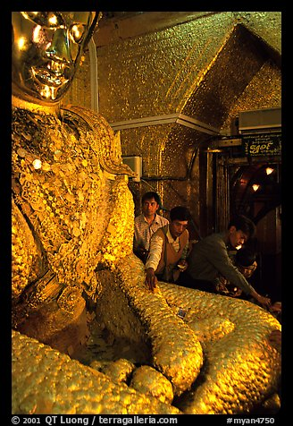 Adding golden leaves to the venerated Mahamuni image. Mandalay, Myanmar (color)