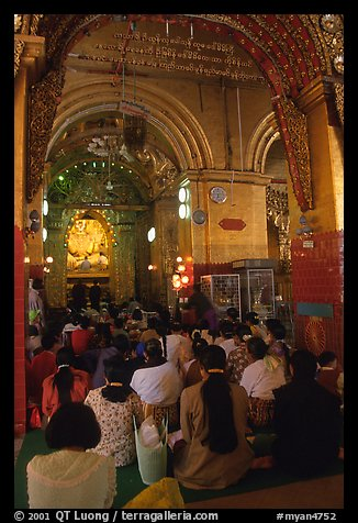 Woman praying at the venerated Mahamuni image. Mandalay, Myanmar (color)