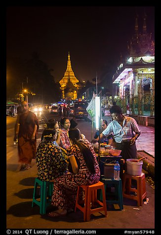 Women eating at street stall at night with Shwedagon Pagoda in background. Yangon, Myanmar (color)