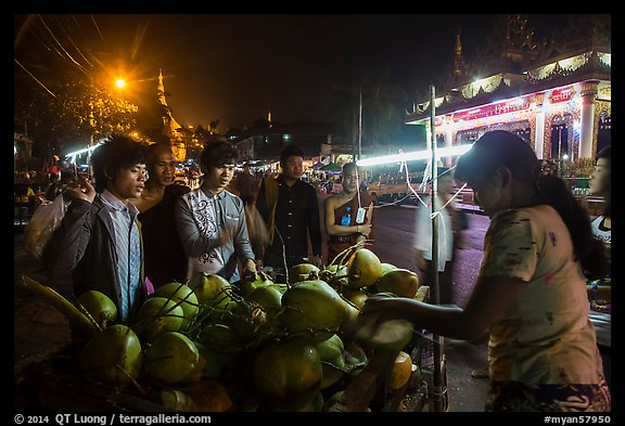 Customers waiting for coconuts to be cut on the street. Yangon, Myanmar (color)